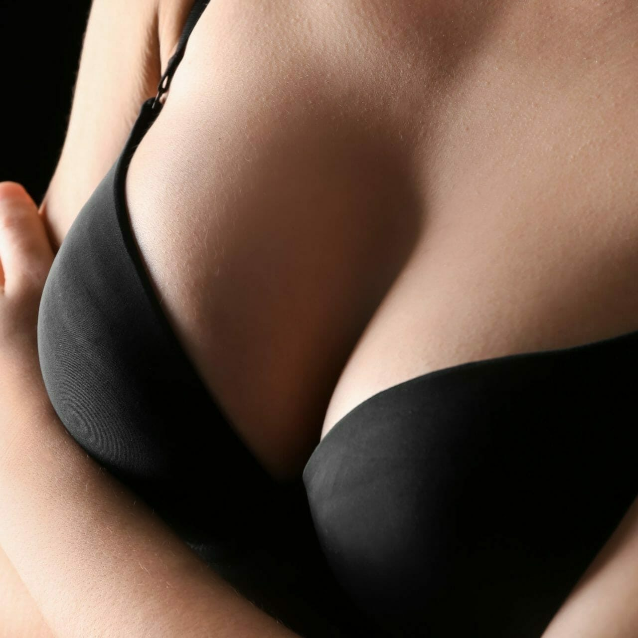 Young woman with beautiful breast on dark background, closeup